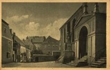 Gryfów Śląski : na pierwszym planie wejście do kościoła, dalej domy na placu kościelnym