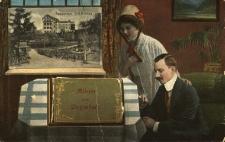 """Głuchołazy : na pierwszym planie kobieta i mężczyzna przyglądający się leżącemu na stole albumowi """"Album von Ziegenhals"""", za oknem widok m.in. na sanatorium """"Waldfrieden"""""""